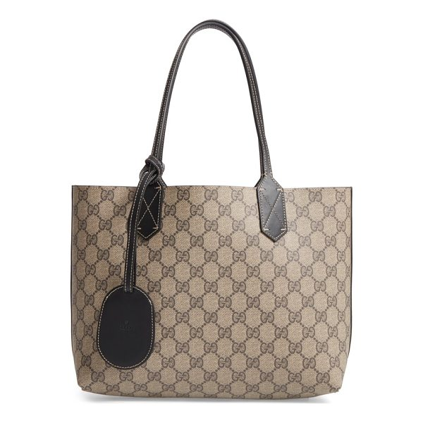 GUCCI small turnaround reversible leather tote - Gucci's signature double-G print reverses to smooth black...