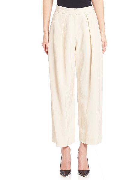 Donna Karan pleated wide-leg pants in natural - Wide leg trousers with crisp pleats. Banded waist. Zip...