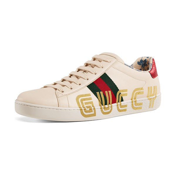 Gucci New Ace Guccy Leather Sneaker in white/gold - Gucci leather sneaker with metallic Guccy in SEGA font,...