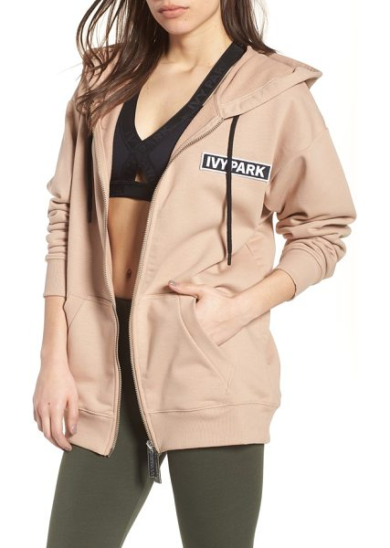IVY PARK badge logo hoodie in sand - A patch emblazoned with the brand's bold logo infuses a...