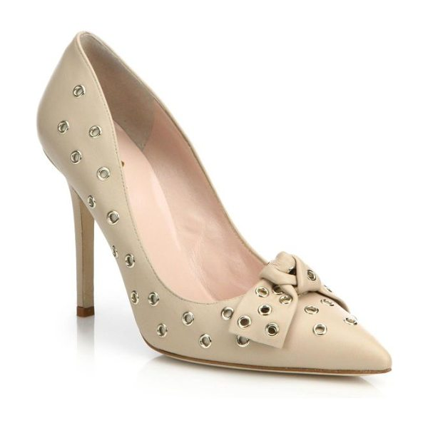 Kate Spade New York Lia grommet leather bow pumps in beige - Bold goldtone grommets punctuate a sleek, point-toe...