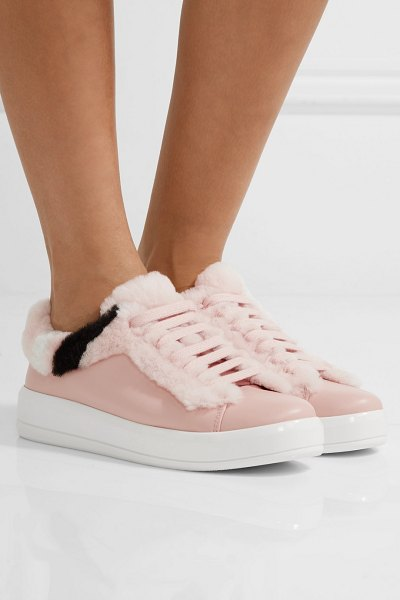 Prada shearling-trimmed leather sneakers in blush - From feathered hoods to tactile belts, fuzziness defines...