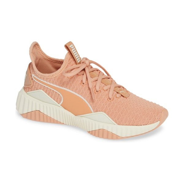 PUMA defy sneaker in dusty coral-whisper white - Sporty ribbing ripples over the top and wraps around the...