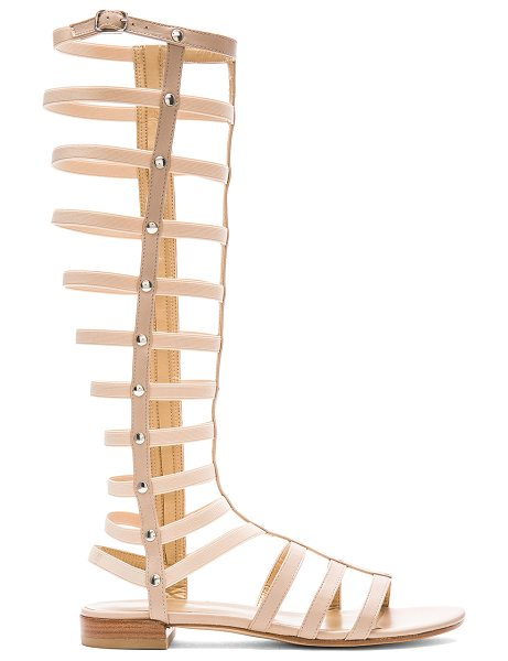 Stuart Weitzman Gladiator Sandal in beige - Leather upper and sole. Buckle accent. Elastic stretch...