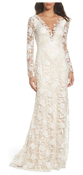 Tadashi Shoji long sleeve a-line sheath gown in ivory/ petal - A gossamer overlay of openwork floral lace brings...