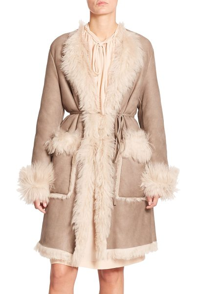 Tomas Maier Belted shearling coat in beige - A slender tie belt defines the waist of this...