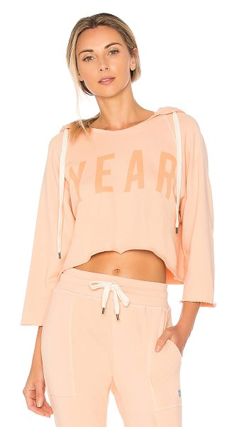 YEAR OF OURS Cropped YEAR Hoodie in peach - 100% cotton French terry. Drawstring hood. Front screen...